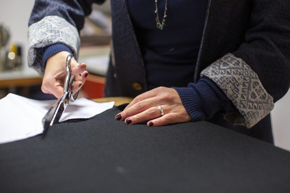 Julie Bonnard coupe un tissu pour confectionner un vêtement