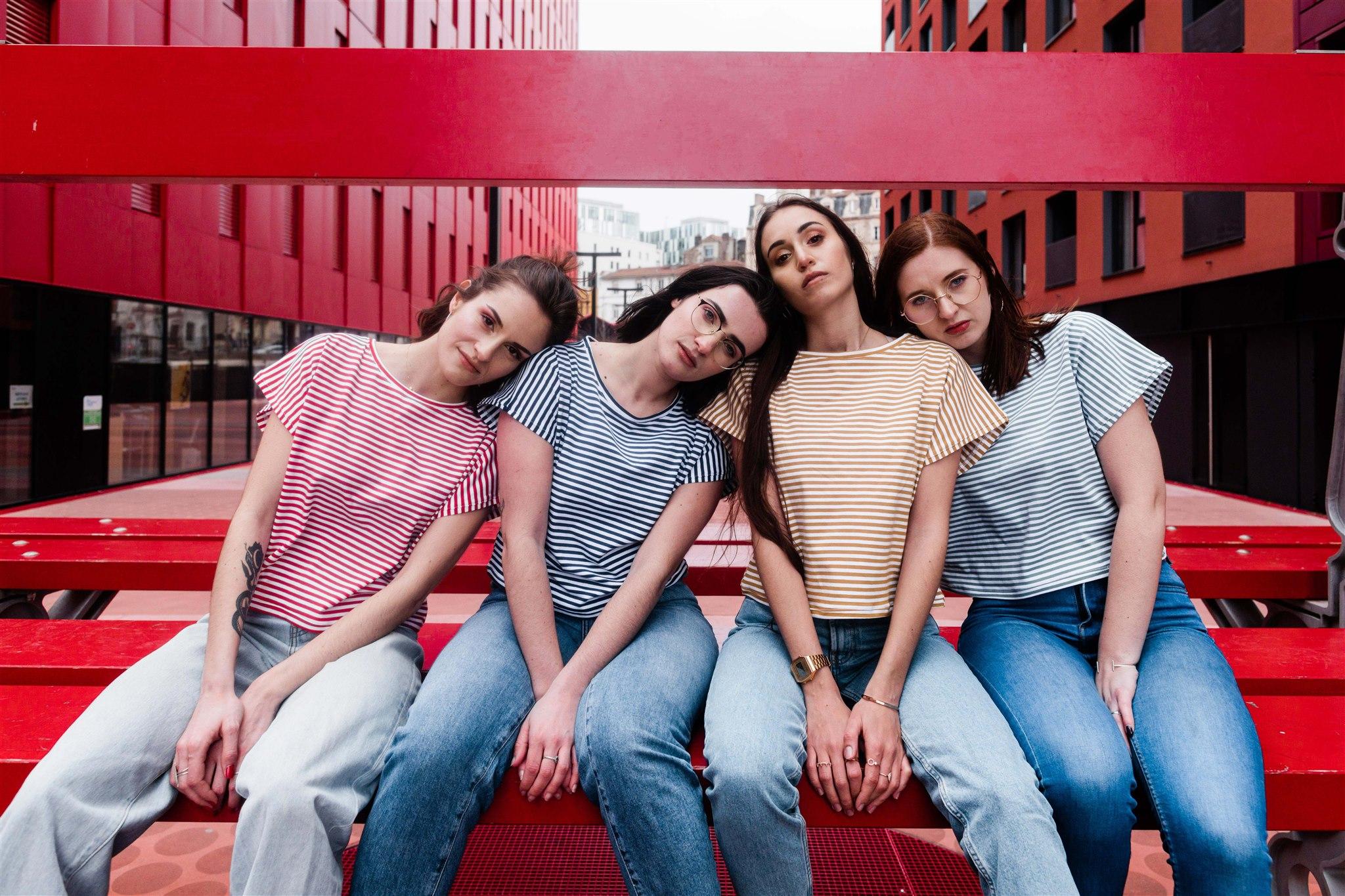 quatre filles assisent sur un banc la tête sur l'épaule de la voisine. Tshirt marinière et jean
